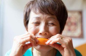Senior Woman Eating Citrus Fruit